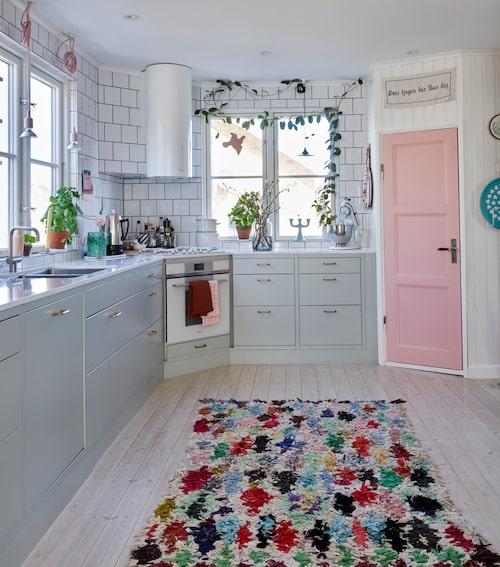 Den färgstarka mattan är pricken över i:et i det charmiga köket och binder ihop rummen där alla rum har stänk av färg. Matta, Casa Marrakech. Kök, Arkitekt plus, Marbodal i kulören lingrön. Fläkt från Faber. Ugn och gashäll, Smeg.