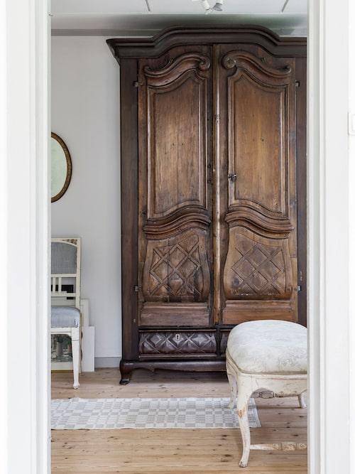 Britta har ärvt det gamla skåpet av sin farmor och farfar. Skåpets dörrar är ytterdörrar från klockargården i Hammarhög. Själva skåpet är tillverkat 1930 av en bysnickare. Taburetten är också arvegods och har troligen tillhört en gustaviansk matsalsmöbel.