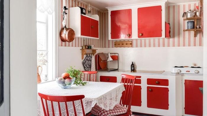 Söta röda köksluckor och matchande tapeter.