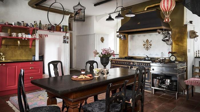 Köket med matbord och vacker stor spis med fläktkåpa i koppar.