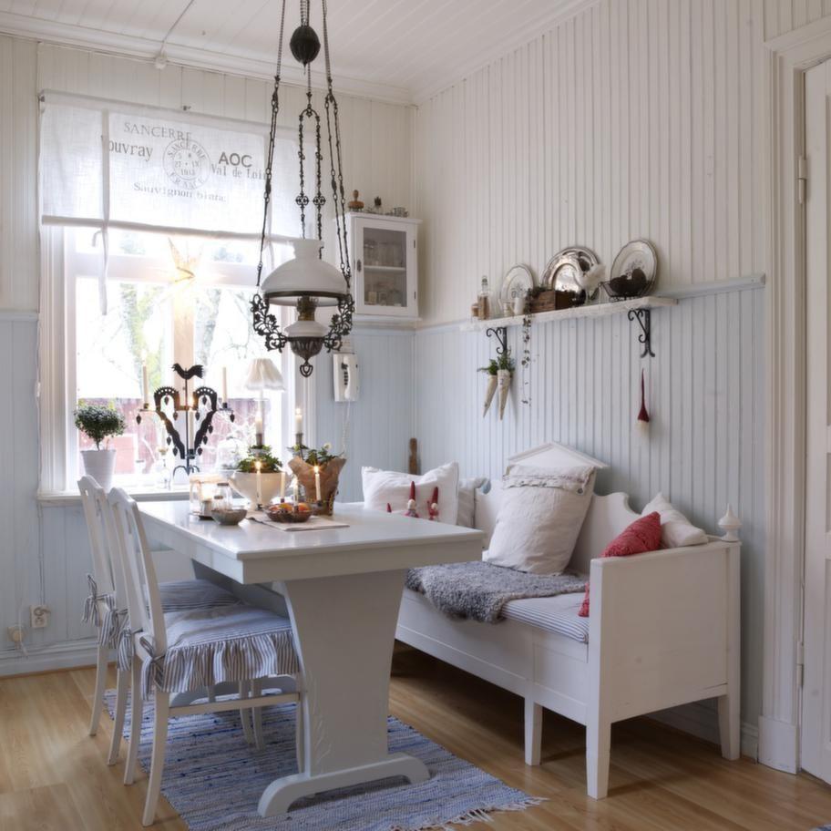 Hemtrevligt. Det ljusblå köket är lantligt med vit kökssoffa, volanger på stolarna och en fotogenlampa i taket.