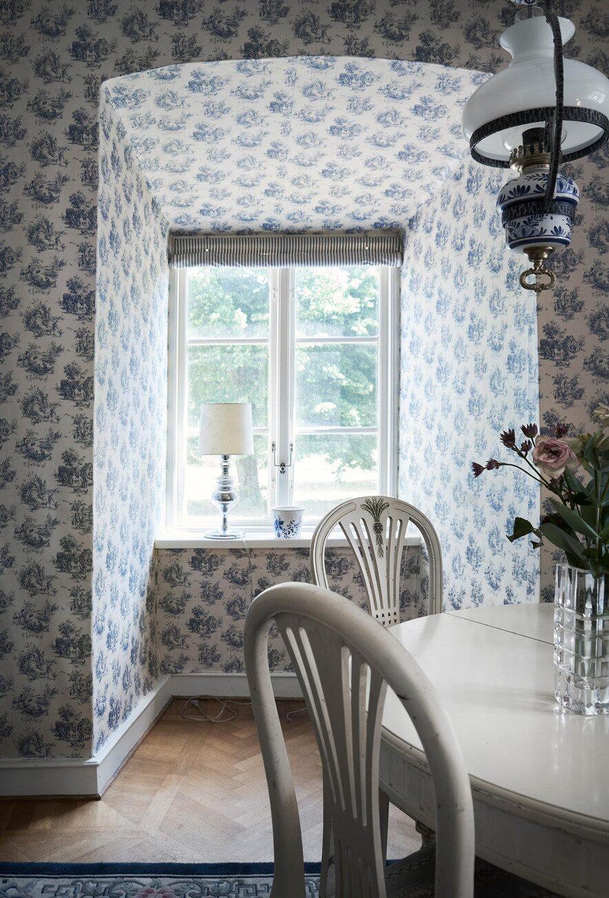 Djupa fönsterkornischer och vacker blåvit tapet.