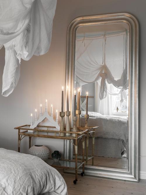 En stor spegel fångar ljus och förstorar rummet. Spegel, Ikea. Blomvagnen är arvegods.