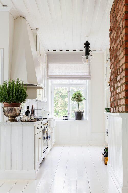 Köket målade Sofia och hennes man om när de flyttade in för tio år sedan. Nu väntar en större köksrenovering. Köksfläkt, Lidhults. Taklampa, antik. Ugn, Ilve. Kruka i fönstret och kruka (champagnekylare) på bänken, Day Home.