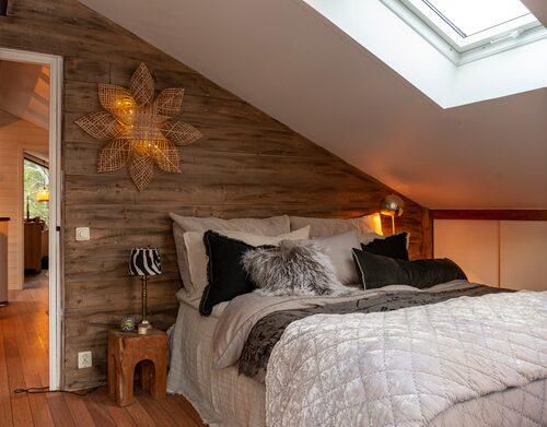 Parets mysiga sovrum ligger på övervåningen, där även barnens sovrum finns. Snedtaken tillför en personlig och mysig charm. Väggen är tillverkad av råspont som behandlats med drivvedsbets från Jotun. Rottingjulstjärna, PR Home.