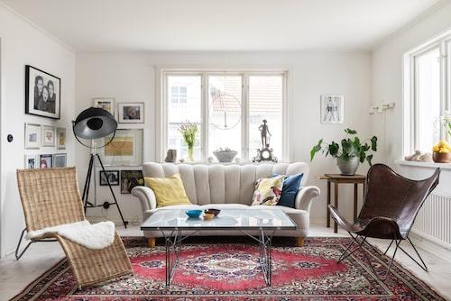 Vardagsrummet är ljust och ombonat. På golvet ligger en av Hanna och Björns första gemensamma investeringar, en handknuten turkisk matta. Den svensktillverkade soffan från 1940-talet är arvegods och omklädd av Tapetsör Wennesjö. Liggfåtölj och soffbord, Moment, Ikea. Golvlampa, Dome, Malmbergs.
