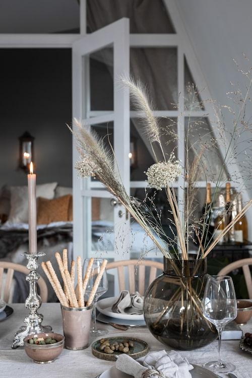 Jenny och Jonas älskar att låta årstiderna synas inomhus och inreder gärna med säsongsbetonade växter. På matbordet syns vilda växter i en glasvas från Ernst. Silverljusstaken är köpt på loppis.