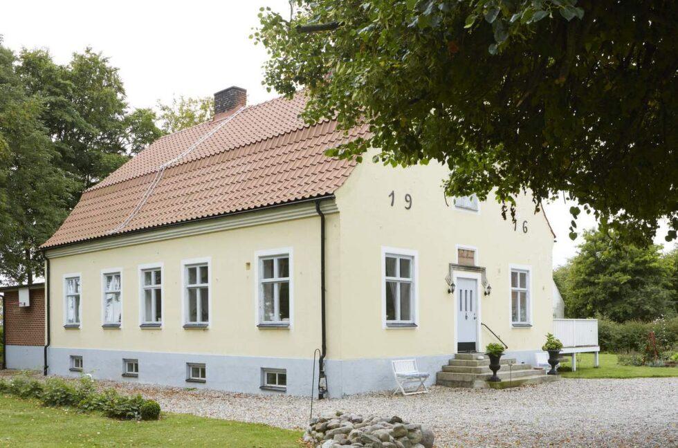 Huset har en klassisk form och brutet tak klätt med tegel.