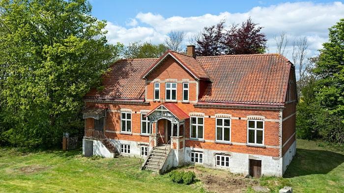 Med både hög fot och rejäla frontespiser på båda långsidor påminner huset om en herrgård.