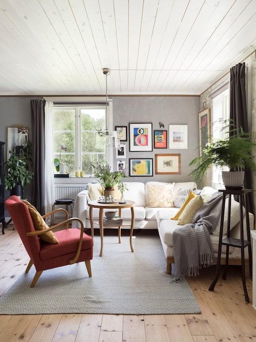 I vardagsrummet har Linda gjort om två Blocketfyndade soffor, Karlstad från Ikea, till en hörnsoffa och inrett med många auktionsfynd. Ullmatta, Ellos. Taklampa av Margot Barolo.
