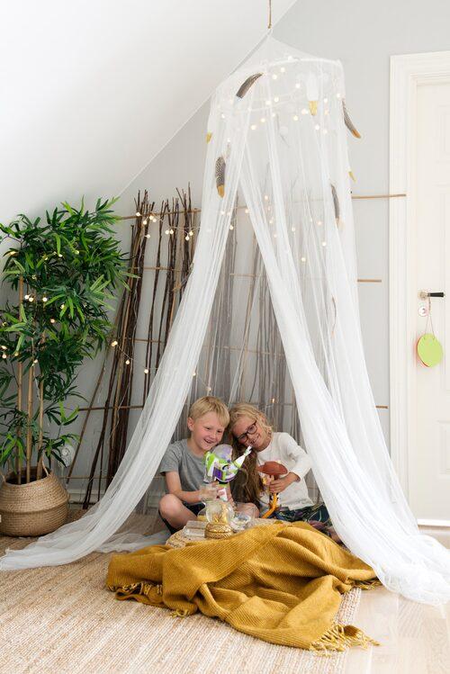 I ett hörn på övervåningen leker Sofie och Alvin. Sänghimmel, Ikea. Gul filt, Klippan Yllenfabrik. Spalje, egentillverkad av pilsly.