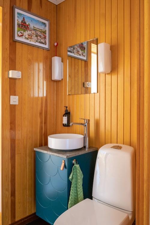 När toaletten på entréplan fräschades upp valde paret att bevara originalväggarna i trä. Kommod, Ikea med front från Superfront. Kalkstensskiva, Thorsbergs Stenhuggeri. Vägglampor, original från 1968.
