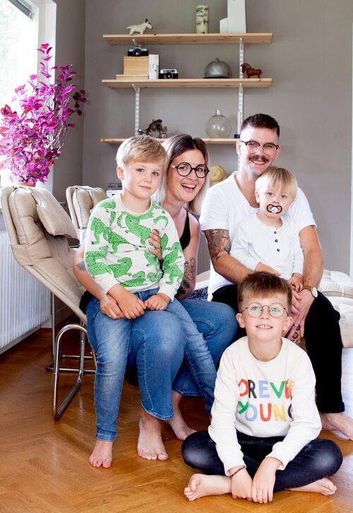 Hela familjen Gamberg-Johansson i vardagsrummet. Mamma Frida med Bosse i knät och pappa Johannes med Cornelis i knät. Frank sitter på golvet.