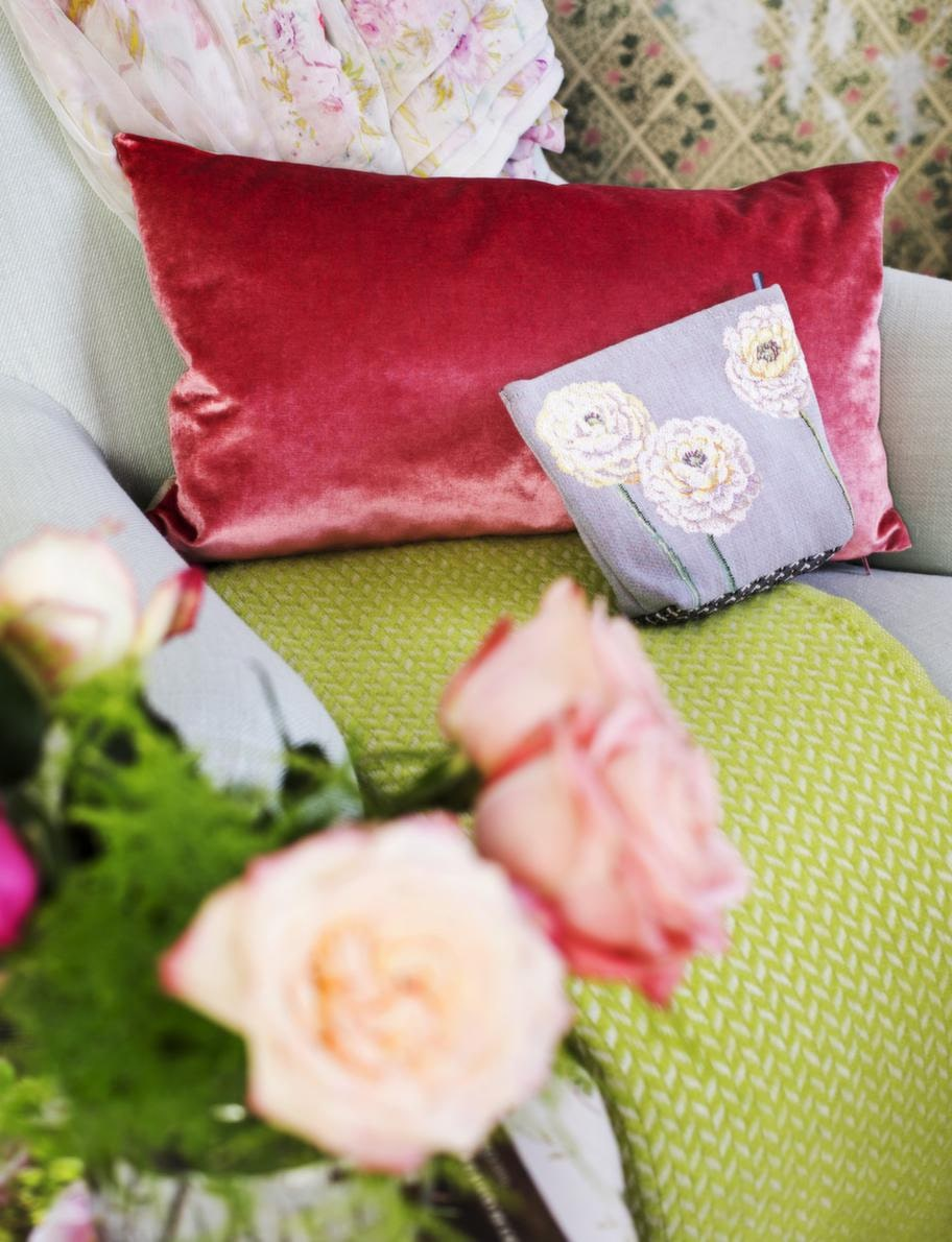Grön pläd från Klippan, 650 kronor, rosa kudde, 495 kronor, necessär med blommor, 395 kronor, allt från Gertrud. Blommigt chiffongtyg, 150 kronor per meter, Rajas.
