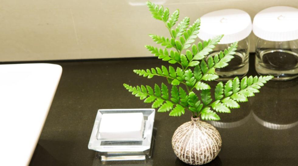 Sätt en vas med en enkel kvist på handfatet eller ställ en krukväxt på en träpall eller annan yta.