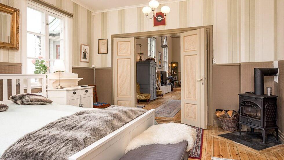Genom dubbla spegeldörrar från salen skrider man in i husets härliga sovrum. Detta är ett master bedroom i ordets rätta bemärkelse med spatsiösa ytor, fönster mot två väderstreck och en härlig liten braskamin samt dörr som leder vidare in till köket.