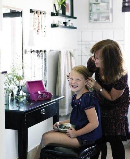 Familjemys. Annica som är gammal frisör pysslar om dottern framför sminkbordet. Det gamla bordet gör att badrummet känns ombonat och ger plats för både egentid och umgänge.