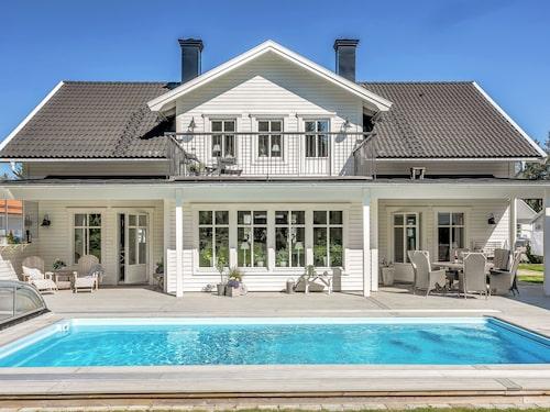 Stort trädäck och flera uteplatser runt poolen i den här arkitektritade villan.