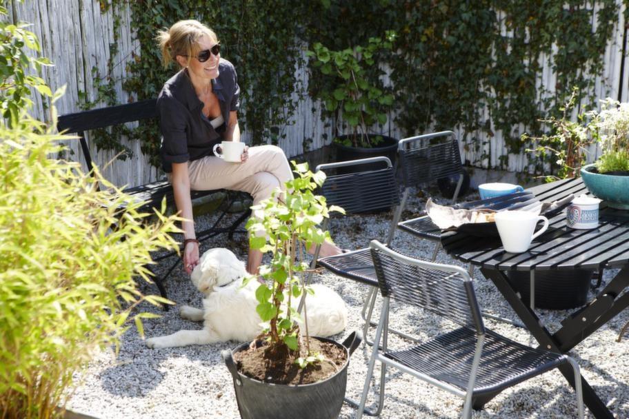 Avkoppling.<br>Johanna Ekelund och valpen Bryan vid trädgårdens tredje uteplats. Bord från Bolagret, stolar från Ikea. Gummikruka från Nessla inredning.