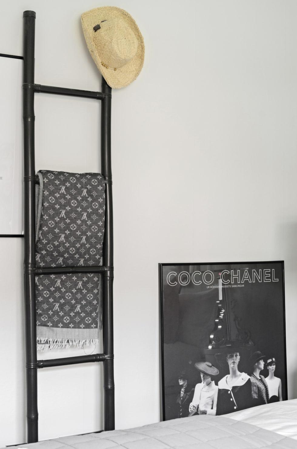 En stege blir en fin väggförvaring i sovrummet. På golvet ett svartvit Chanel-plansch.