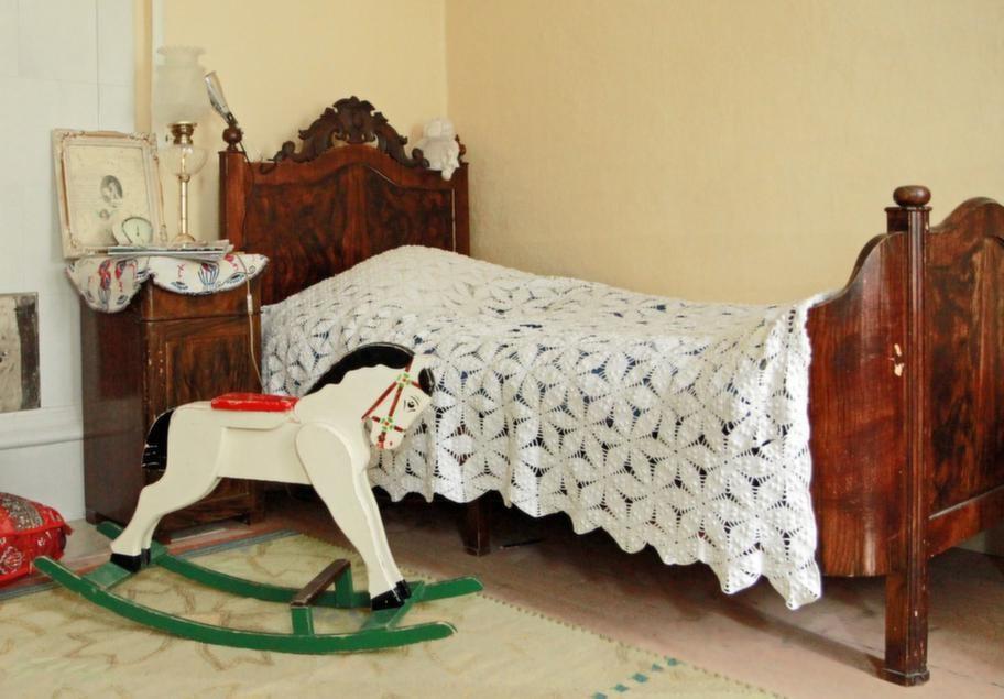 Rustik säng för gästerEtt av gästrummen i Karins hus. Gunghästen och den gamla imperialsängen har Karin köpt på auktion.