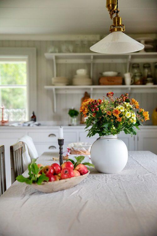 Höstfint i köket med äpplen och blommor i en vas från Ernst. Skomakarlampan från Klassiska byggvaror.