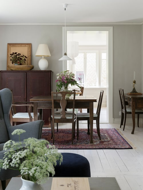 I det stora vardagsrummet ryms även en matsalsgrupp. Skåp, matsalsmöbler, skrivbord och skomakarlampa följde med huset. Vit bordslampa, loppisfynd. Vas, Ernst form.
