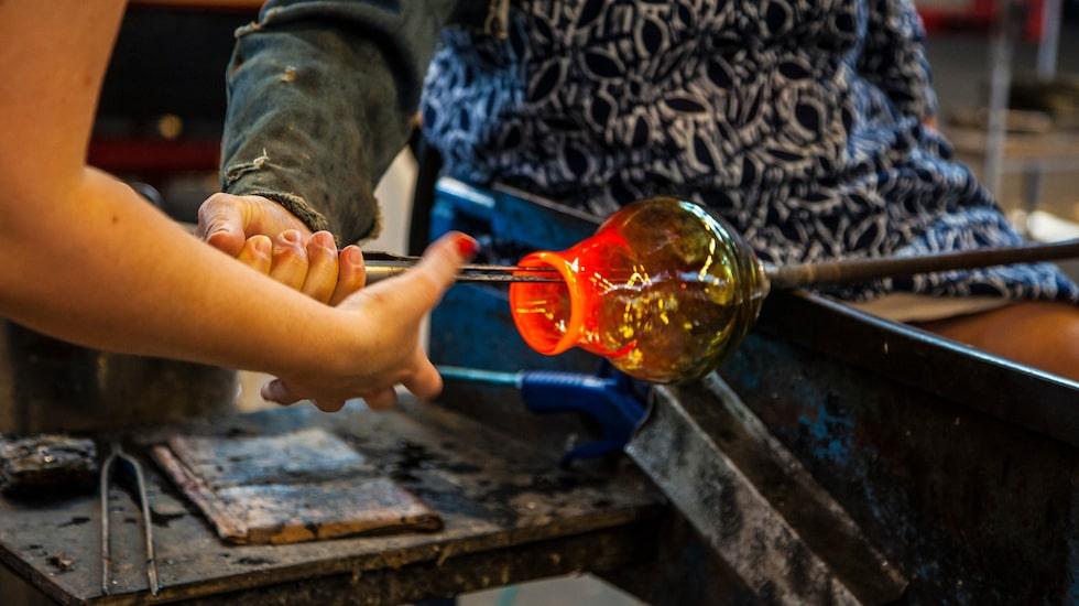 Det går fint att forma den trögflytande, brännhett orangeröda glasmassan med en blöt träskopa.