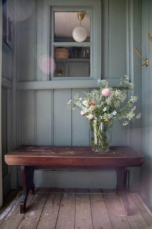 Helena fyller gärna huset med blommor. Vid spegelfönstret i hallen satt det tidigare ett riktigt fönster och familjen planerar att sätta in ett fönster på sikt. Bänken och vasen är fyndade på loppis. Taklampa, Ikea.