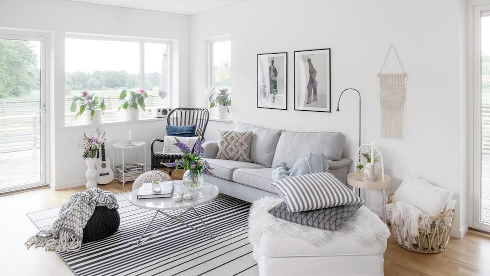 Mjuka filtar och många kuddar bjuder in till avkoppling i det luftiga, ljusa vardagsrummet. Svart fåtölj, Ikea. Tavlor, Arty Swede.