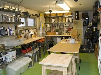 EFTER: utmärkt arbetsplats. En ny grön färg på golvet, förvaringssystem, Broder, Ikea, med hyllplan i gallerplåt rymde många transparenta lådor i plast, Samla, Ikea. Glasburkar, metallboxar, zinktunnor gör att verktyg och andra lösa småprylar kan sorteras och stuvas undan. Stora krokar, Regel, Ikea, går att hänga trädgårdsmöbler och redskap på. En skiva på bockar mitt i rummet ger en utmärkt arbetsplats, som också går att flytta undan om det behövs.