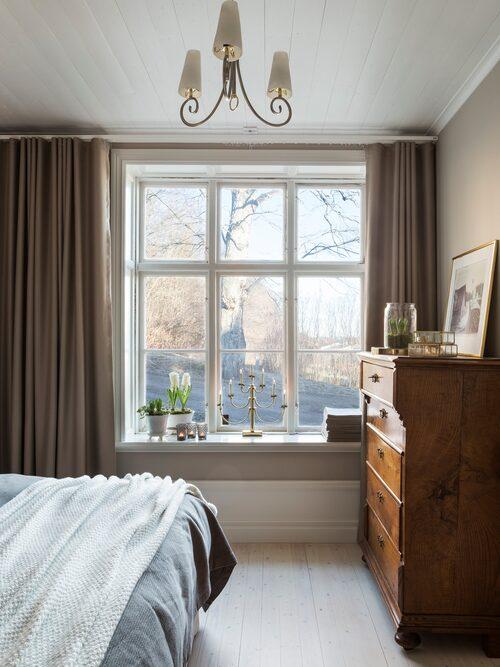 Familjens sovrum är inrett i vilsamma toner. Sängkläder, Hemtex. Sängkappa, Åhléns. Taklampan är från Irland. Byrån i ek är från slutet av 1800-talet och köpt på auktion. Smyckesskrin och ljuslykotor, Hemtex.