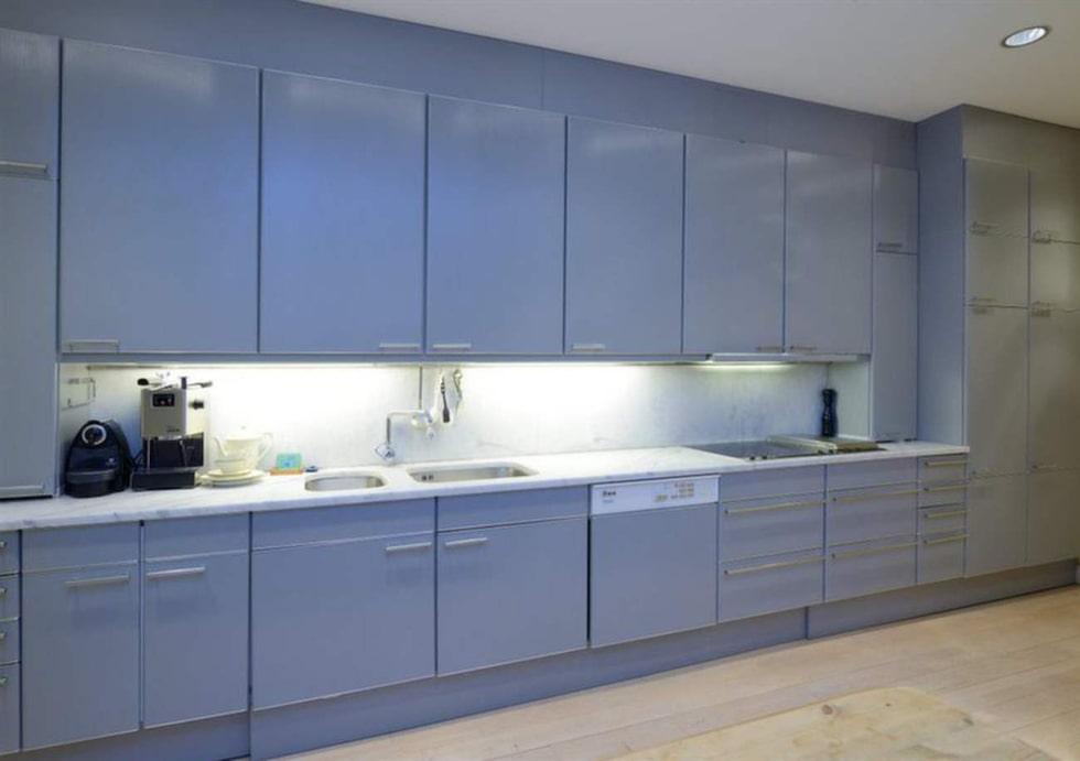 Köket har arbetsskiva och stänkskydd i ljus carrarramarmor.