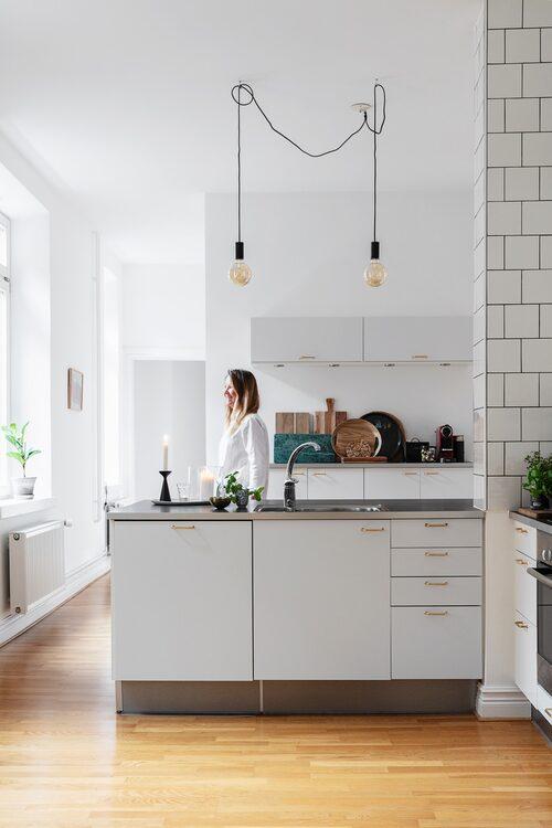 När familjen tog över lägenheten gjordes en mindre köksrenovering. Beslag byttes ut, skåpsluckor och lådfronter lackerades om och väggen kläddes med kakel. Köket har en liten bardel men är i övrigt ett arbetskök.