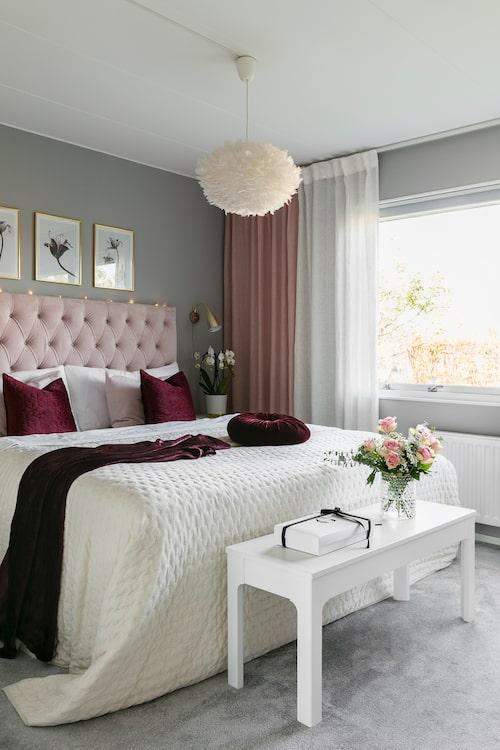 I Sabinas och Jans sovrum matchas rosa med dovt vinrött för en mer lugn och dämpad känsla. På golvet ligger en heltäckningsmatta från Kilandsmattor. Säng från Ikea med sänggavel från Ellos. Överkast, Jotex. Kuddar och pläd, Rusta. Bänk Ikea. Vas H&M Home. Sänglampa, Jotex. Taklampan har Sabina gjort själv.