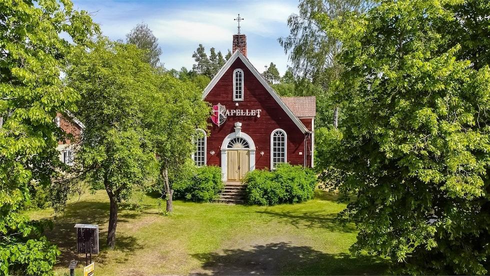 Det röda vackra kapellet ligger omgärdat av grönska.