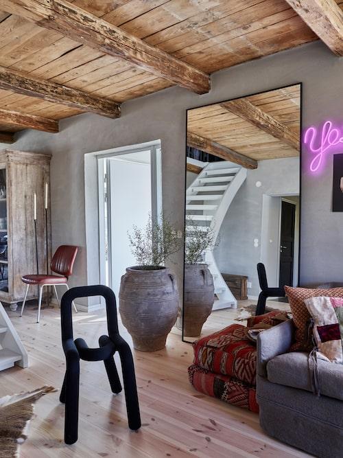 Den stora spegeln skapar reflektioner och rymd i vardagsrummet. Spegeln har Anna måttbeställt av Glasorama i Landskrona. Svart stol Bold Chair, Moustache, stolen i skinn är en gammal frisörstol, ett Blocketfynd. Yes-lampa, Lagerhaus.