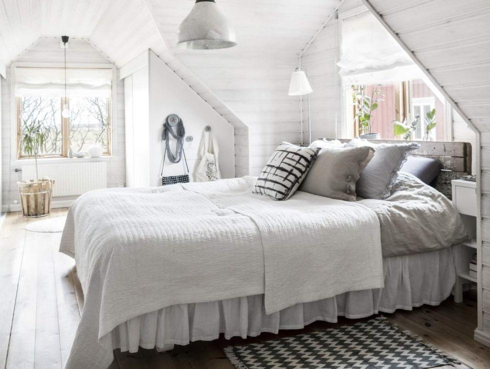 Rogivande sovrum. Egensnickrad sänggavel av gamla plankor. Gaveln ger en skön känsla i rummet. Under snedtaket finns praktiska platsbyggda garderober.