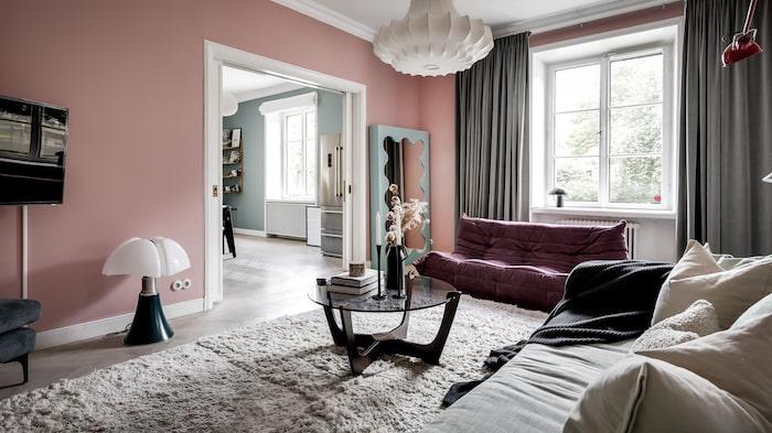 Mysiga rosa väggar i vardagsrummet.