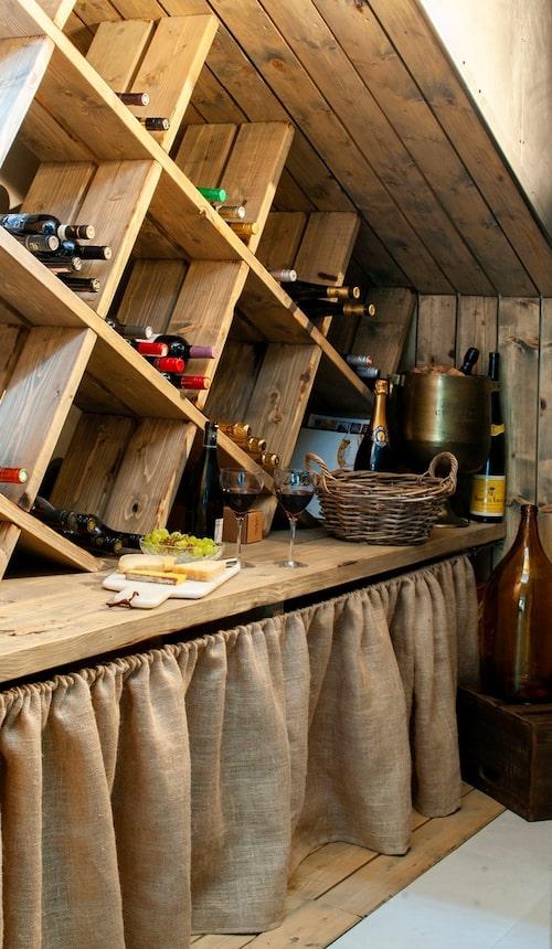 Johan har byggt en vinkällare i utrymmet under trappan. Med hjälp av trä, industriplåt och ett skynke av säckväv har han skapat ett trivsamt och funktionellt utrymme.