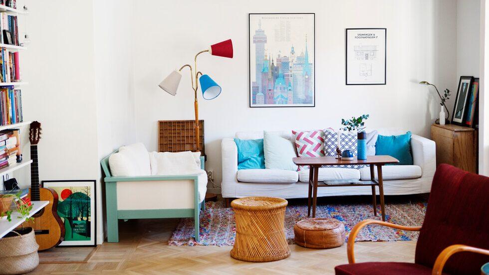 Vardagsrumsdelen ligger i anslutning till köket och här finns även en kamin. Rummet är inrett med soffa från Ikea och ett gammalt teakbord. Kuddar från bland annat H&M home. Soffan till vänster har Katja köpt på nätet och målat i ljusgrönt.