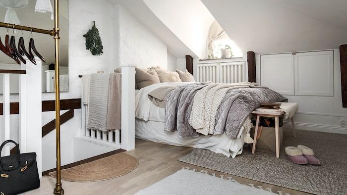 En trappa upp finns sovrummet med snedtak och fönster.