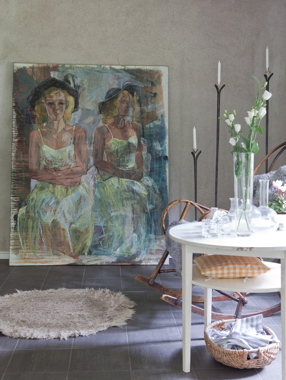 Den stora tavlan är målad av Anna Rabe. Ljusstarkna i järn är nerstuckna i stenar och är designade av Marie.