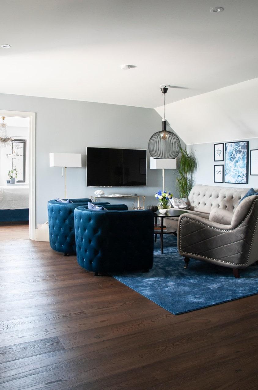 Övervåningen har fått ett mörkare ekgolv som passar fint till inredningen i blått. Ekgolv, Tarkett. Fåtöljer, Soffa direkt.