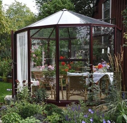 SOMMARTID. Växthuset blev klart i maj. Inredningen är ännu lite provisorisk. Det gäller att känna sig fram till vad som behövs. Rabatterna utanför gjordes i ordning och planterades under sommaren med en stomme av perenner och växter i krukor och ettåringar för att fylla ut.