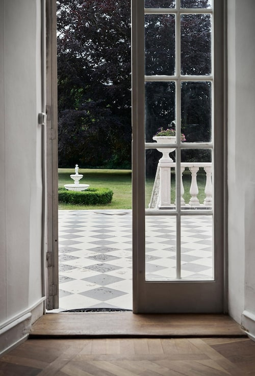 Vacker utsikt genom ett par spegeldörrar mot husets terrass av schackrutig sten.