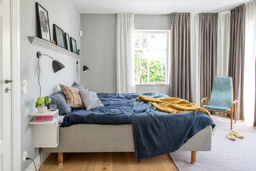 Sovrummet som ligger på nedre plan är målat i en ljusgrå kulör. Sänglampa, Gubi. Sängbord, Maze. Matta, Muuto. Kuddar, Marimekko.