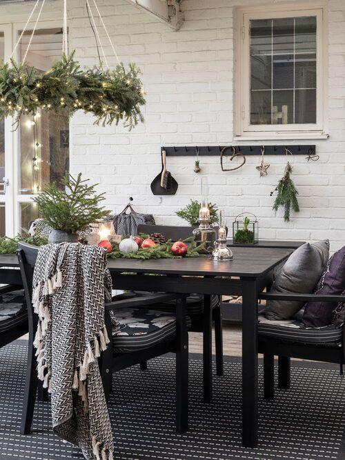 Sofia har dekorerat familjens uterum med röda äpplen, ljus och granris. Matta från Rusta. Ljuskronan har Sofia gjort. Bord och stolar, Ikea.