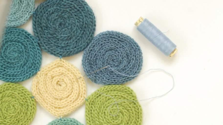Lägg ut alla snurror och börja sy ihop dem med några stygn i sidorna, till en hel matta.