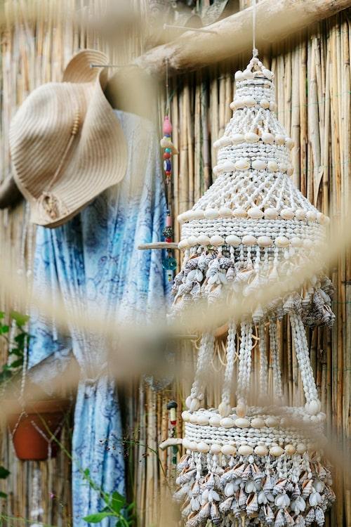 Vid duschen hänger en kimono från Indiska med några år på nacken. Snäckskalslampan är köpt på loppis.